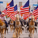 Horsewoman ride in formation with flags during the Fiesta Parade in San Antionio, Texas